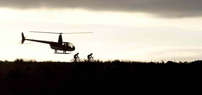 Racers get shadowed by a chopper at the 2010 Cape Epic. Photo by Greg Beadle/SPORTZPICS