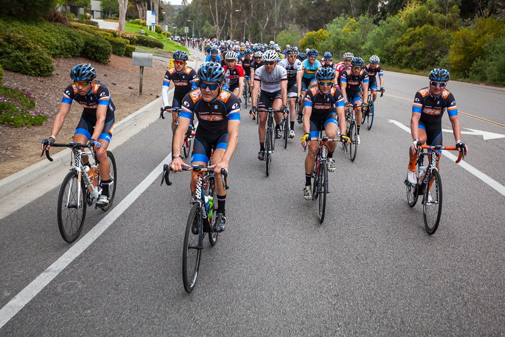 A large group of cyclists biking on a street in California