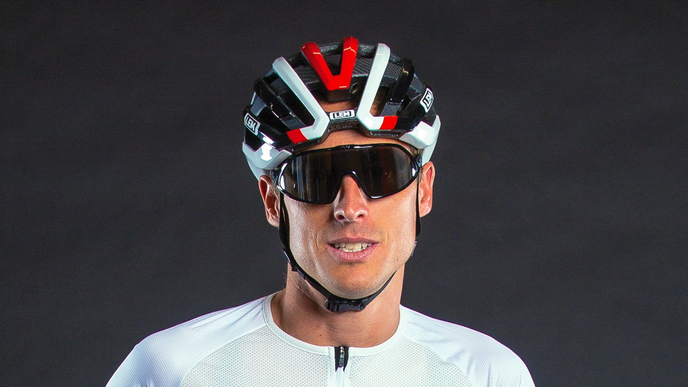 Close-up of man wearing cycling helmet and glasses.