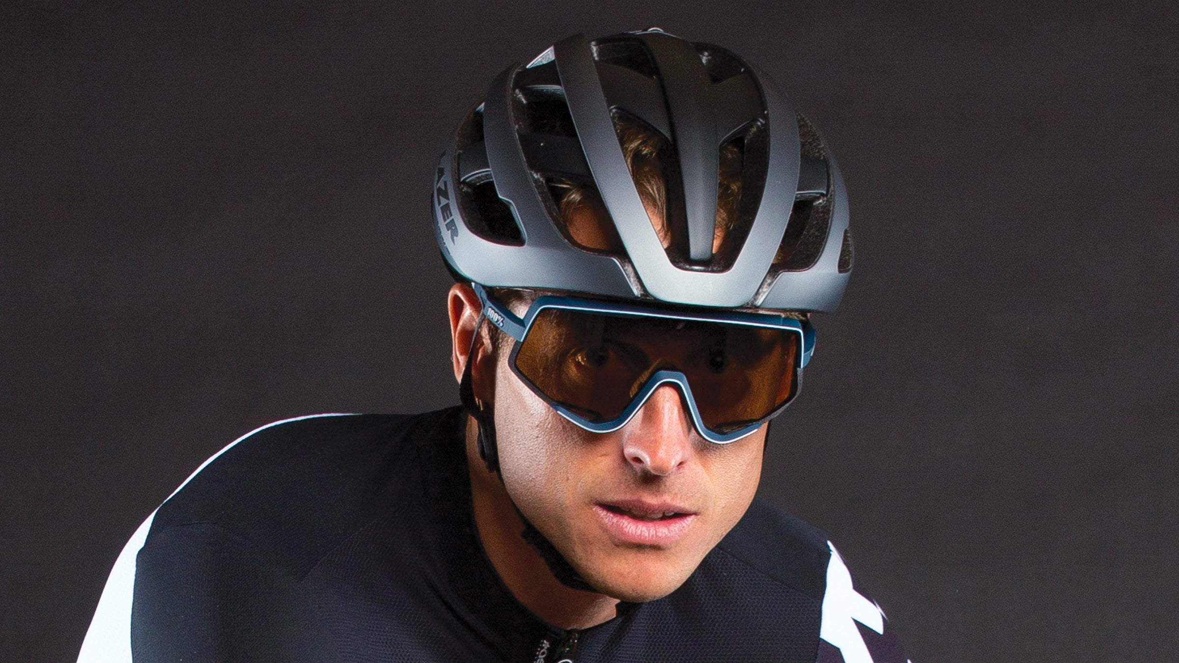 Close-up of man's face with bycicle helmet and glasses.