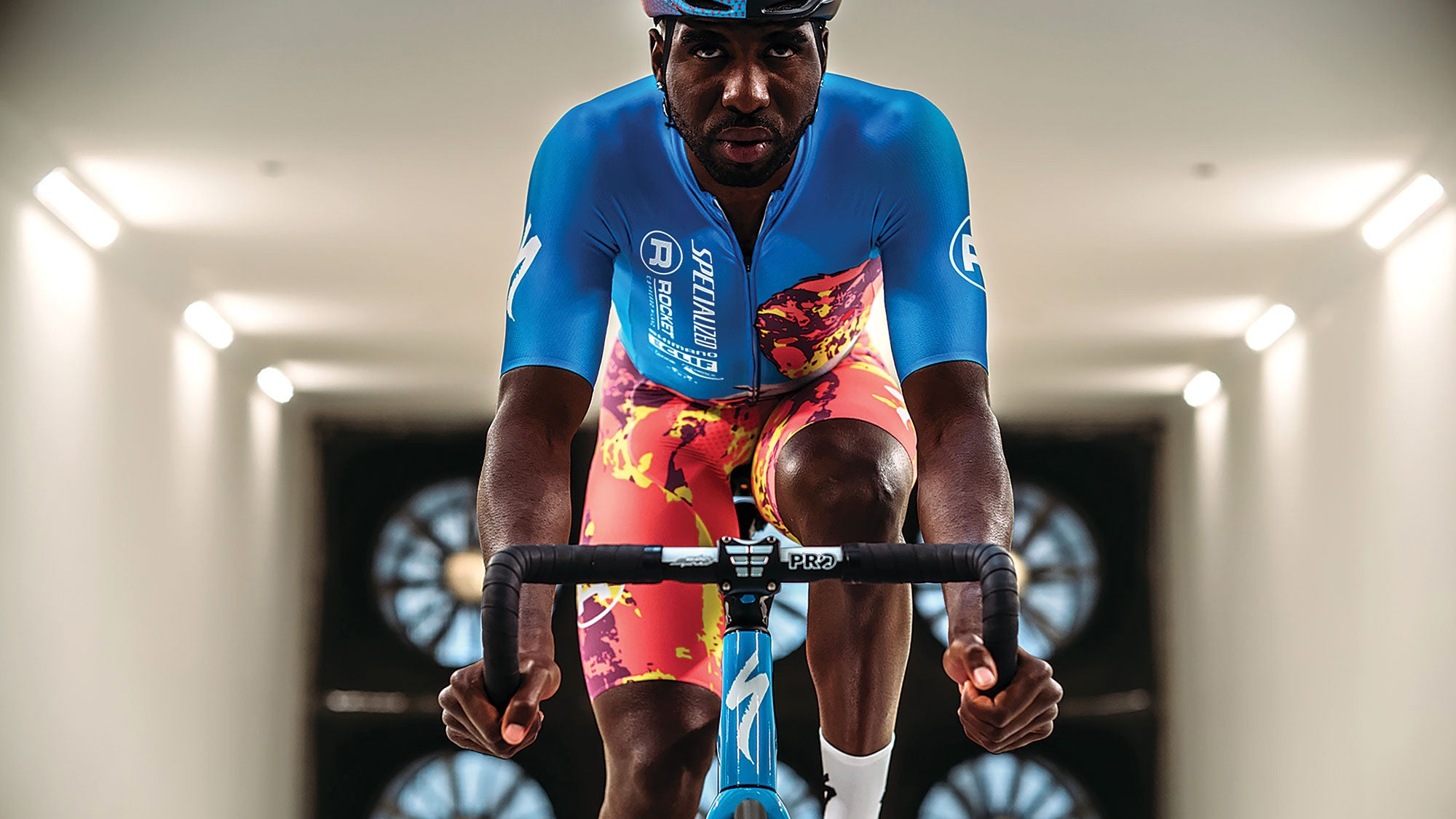 Man facing the camera, riding a Specialized bike on rollers in a wind tunnel