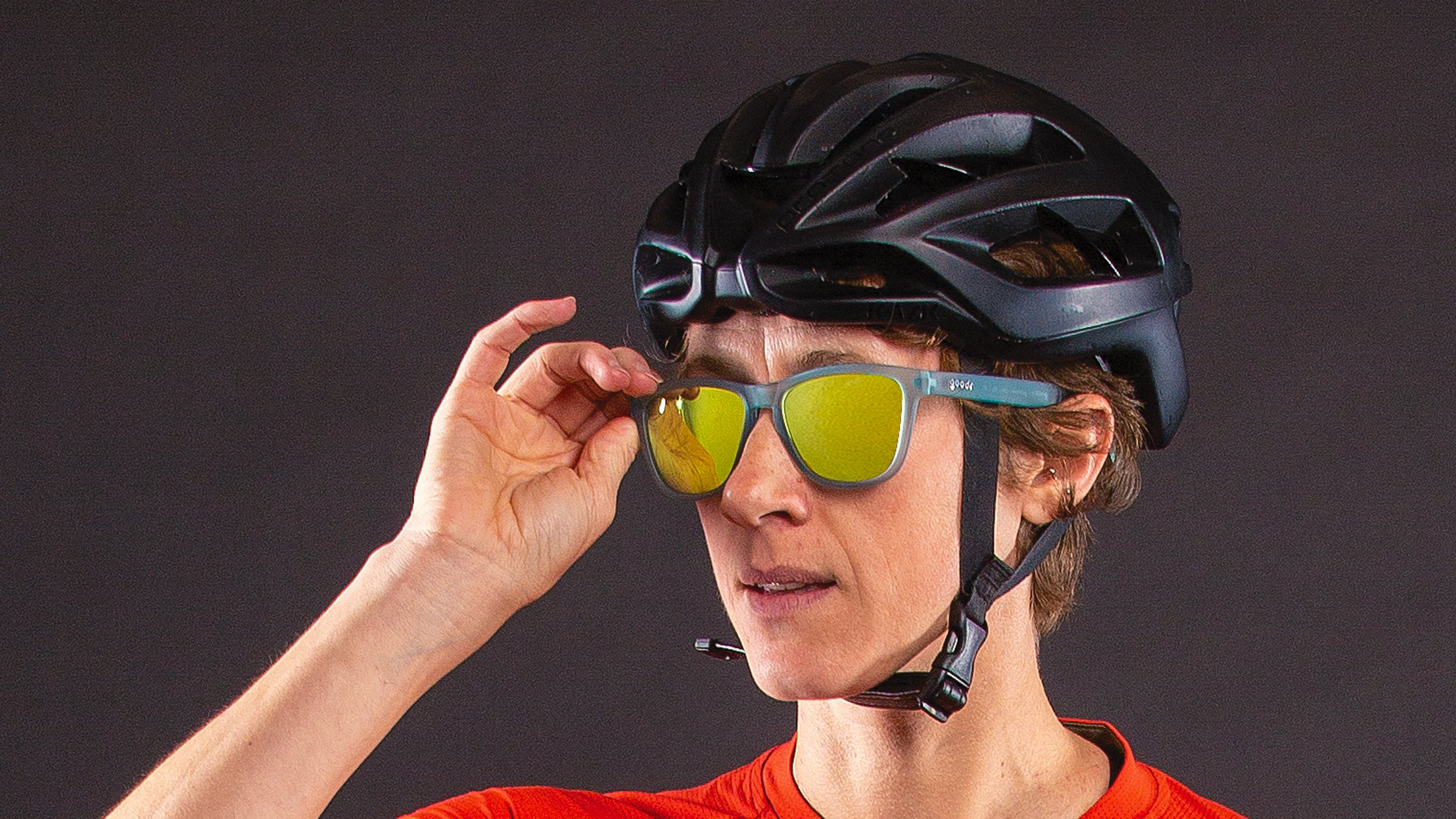 Close-up of woman wearing cycling helmet adjusting her sunglasses