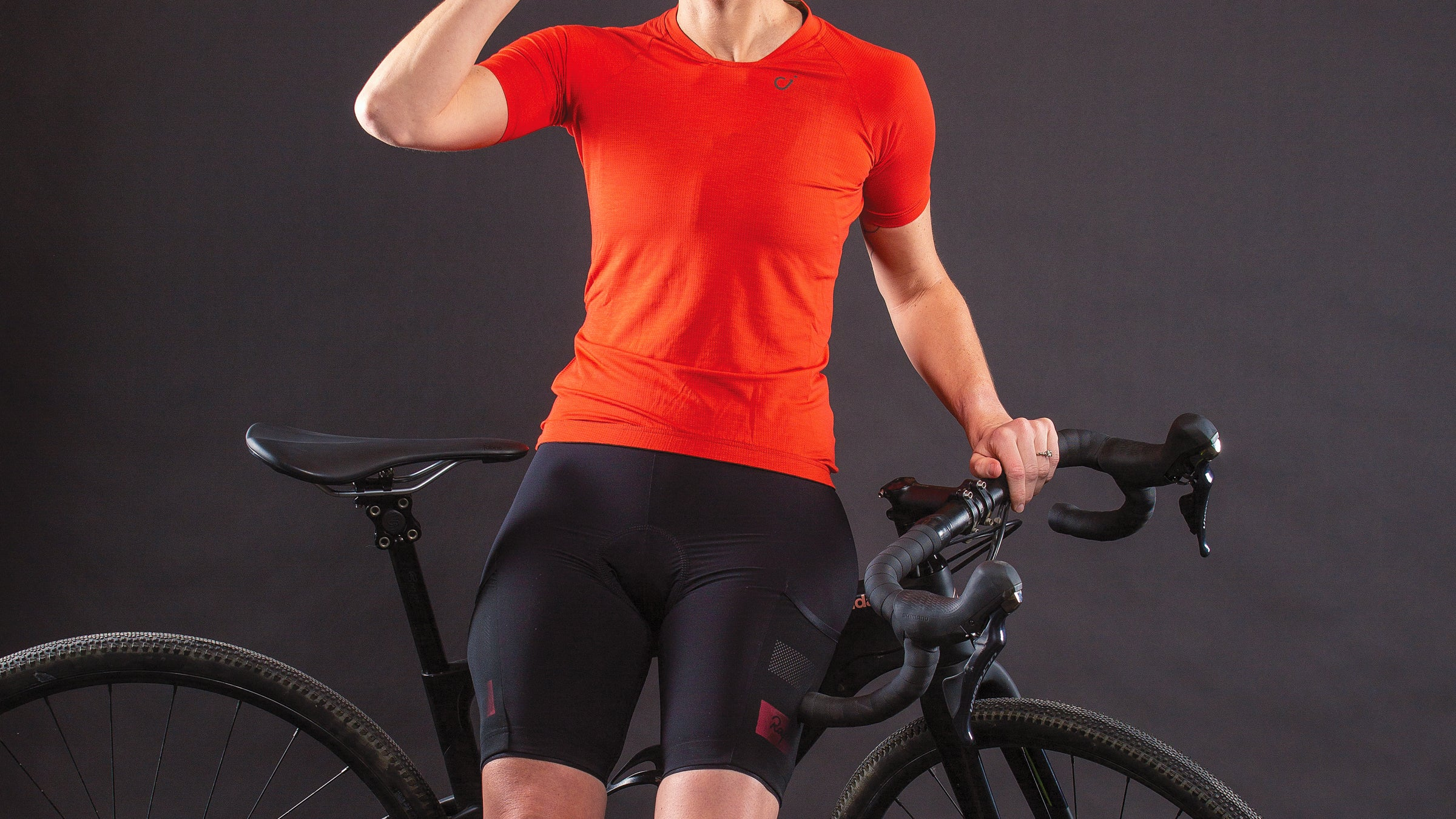 Detail of woman leaning against gravel bike and wearing cycling jersey and bike shorts