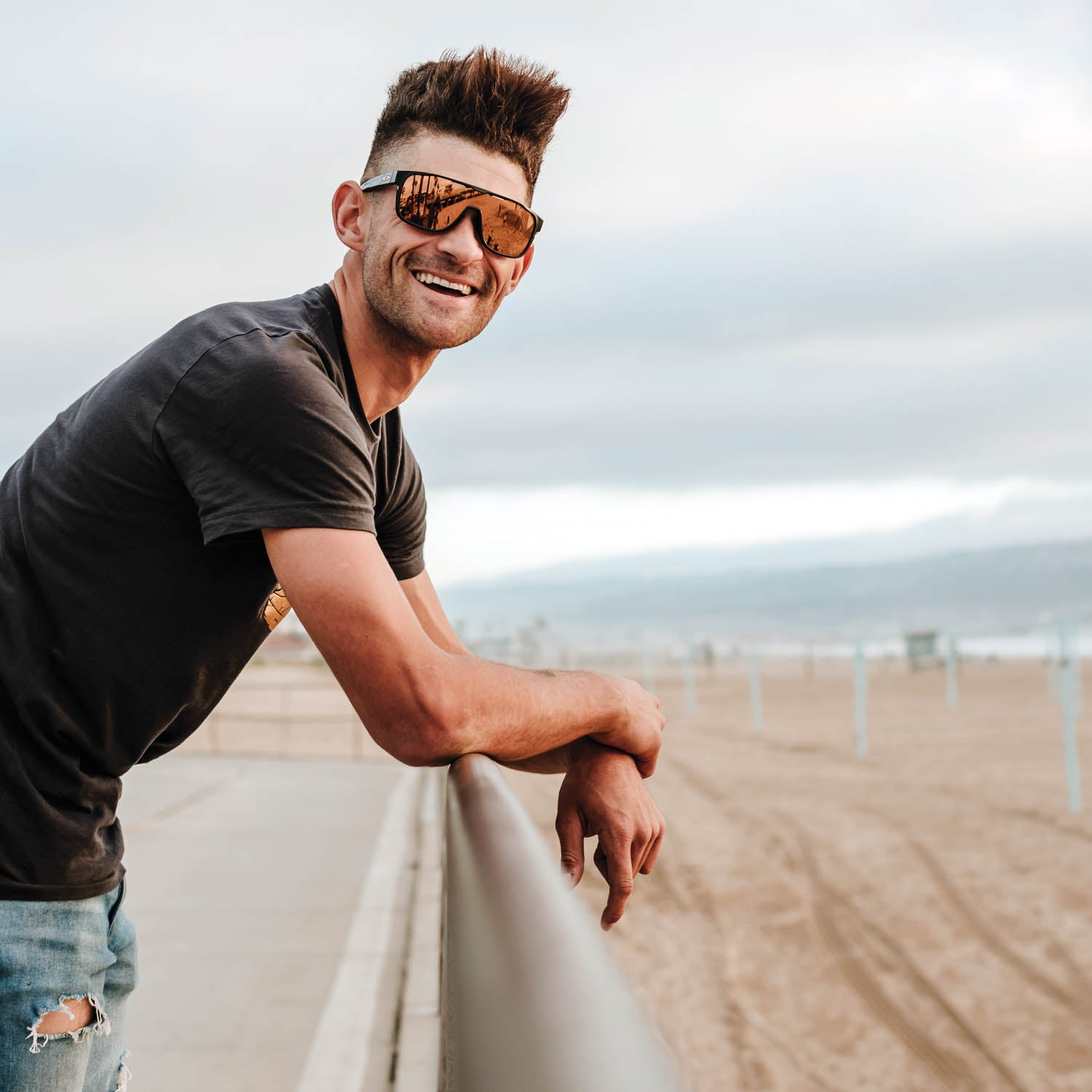 Eamon Lucas wearing sunglasses and leaning on a rail overlooking a beach