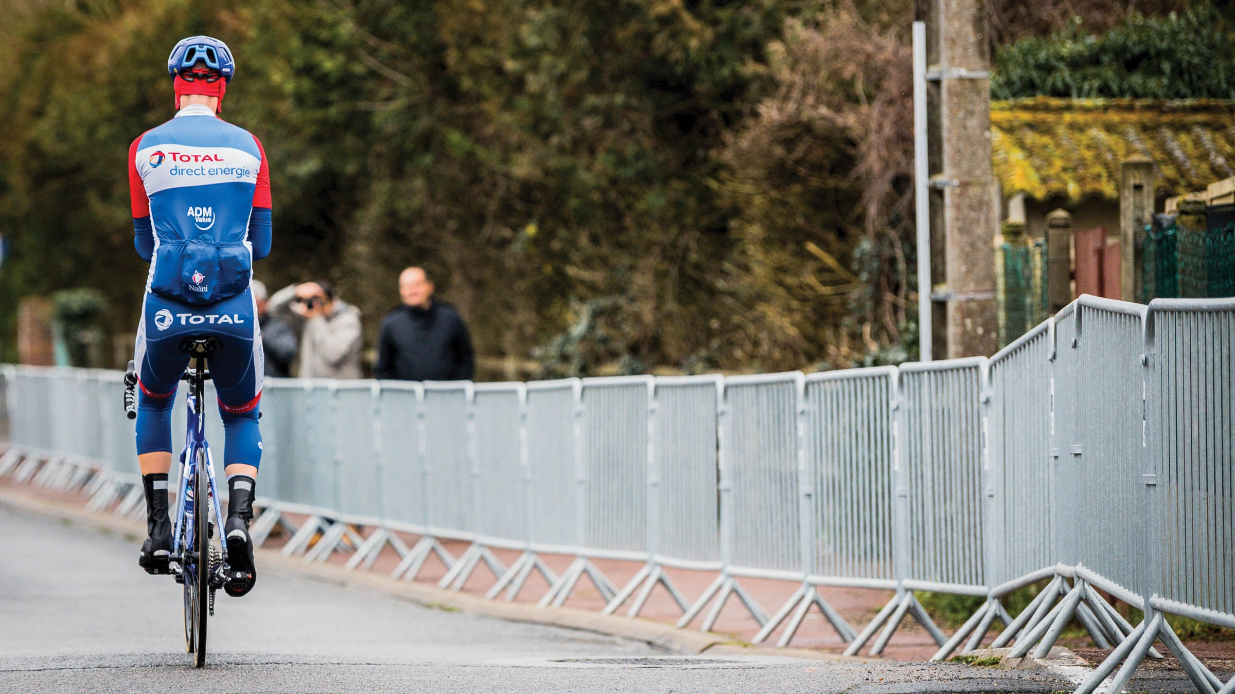 Single cyclist sitting up with back to the camera with metal fencing lining the road
