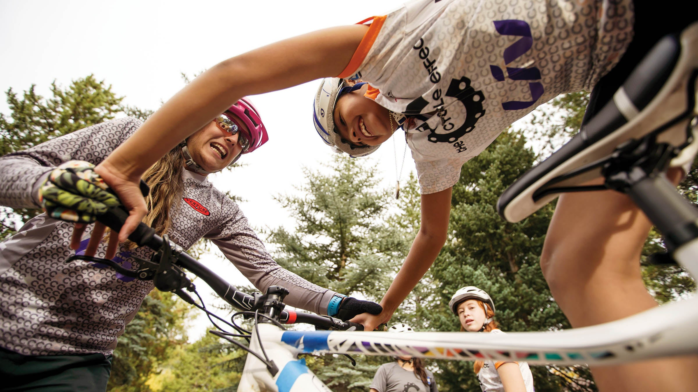 A woman grabs the handlebars of one of the girls' bikes