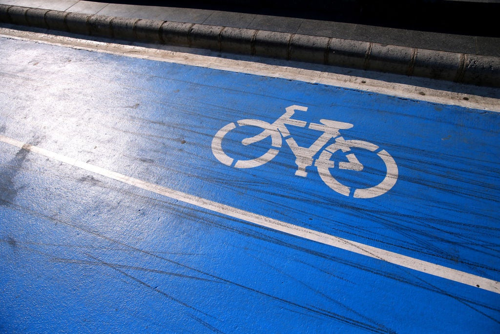 A blue road with a bicycle symbol in the designated bike lane