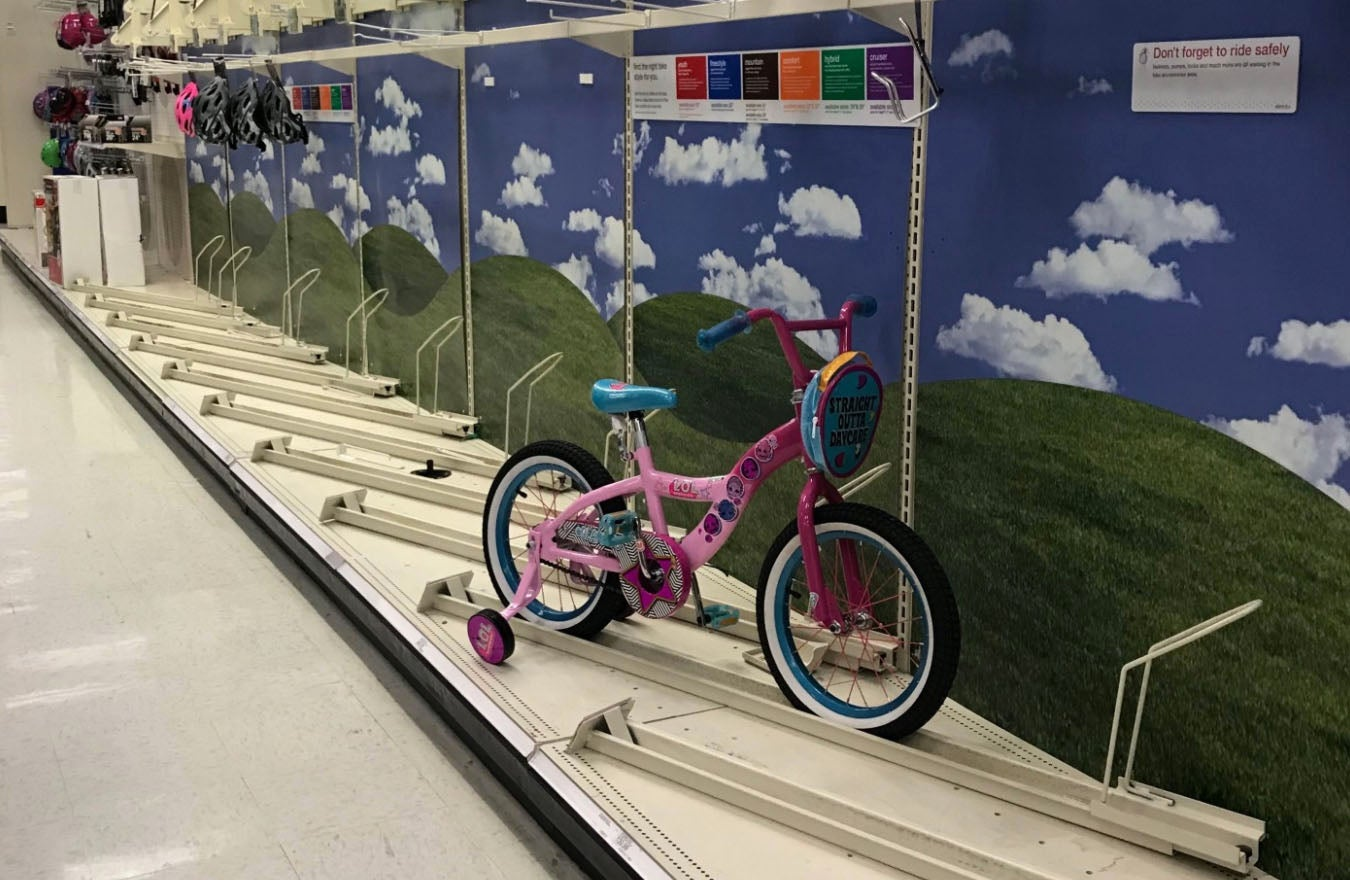 A pink tricycle sits on an otherwise empty bike shelf at Target