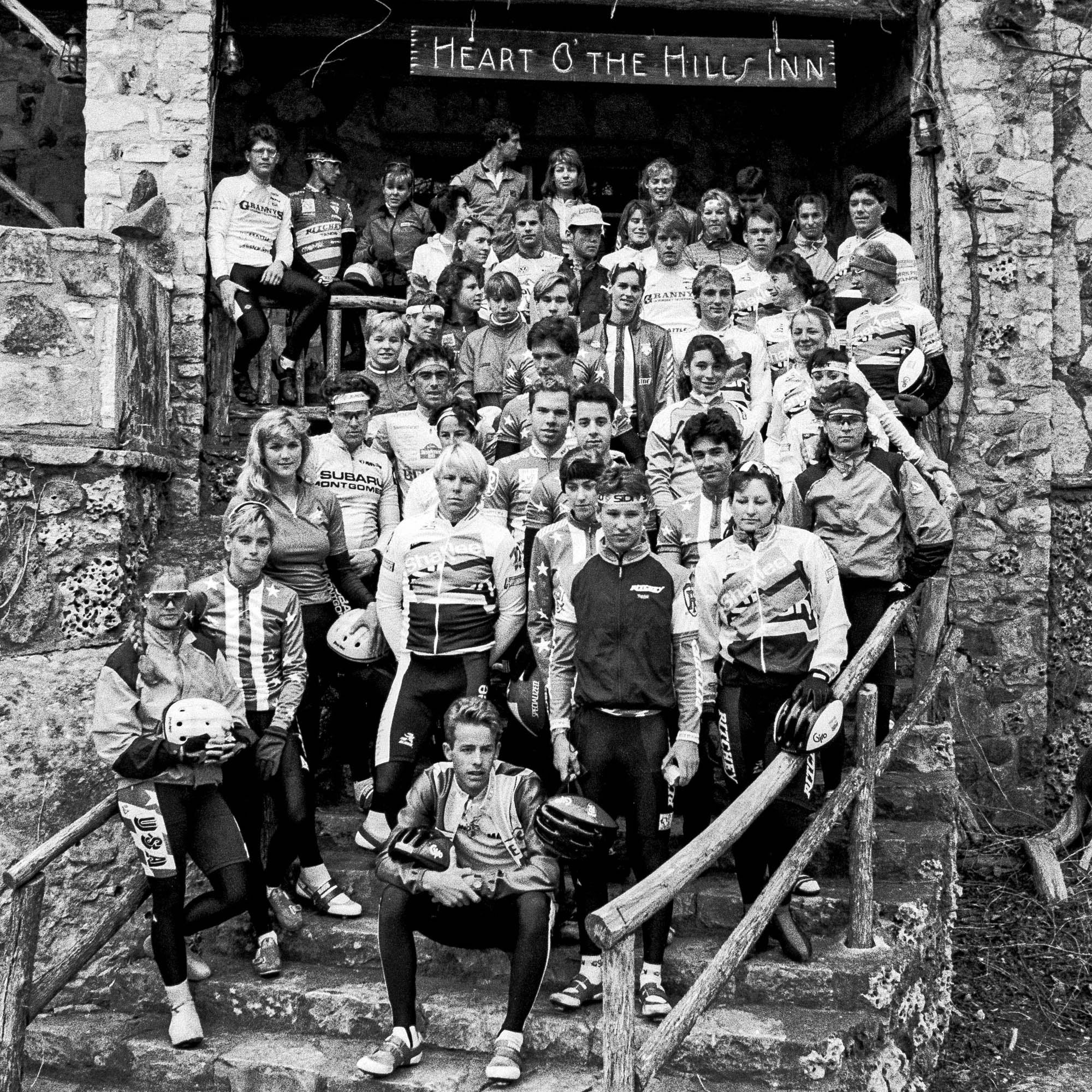 Black & white photo of many athletes in cycling gear standing on the steps of the Heart O' the Hills Inn