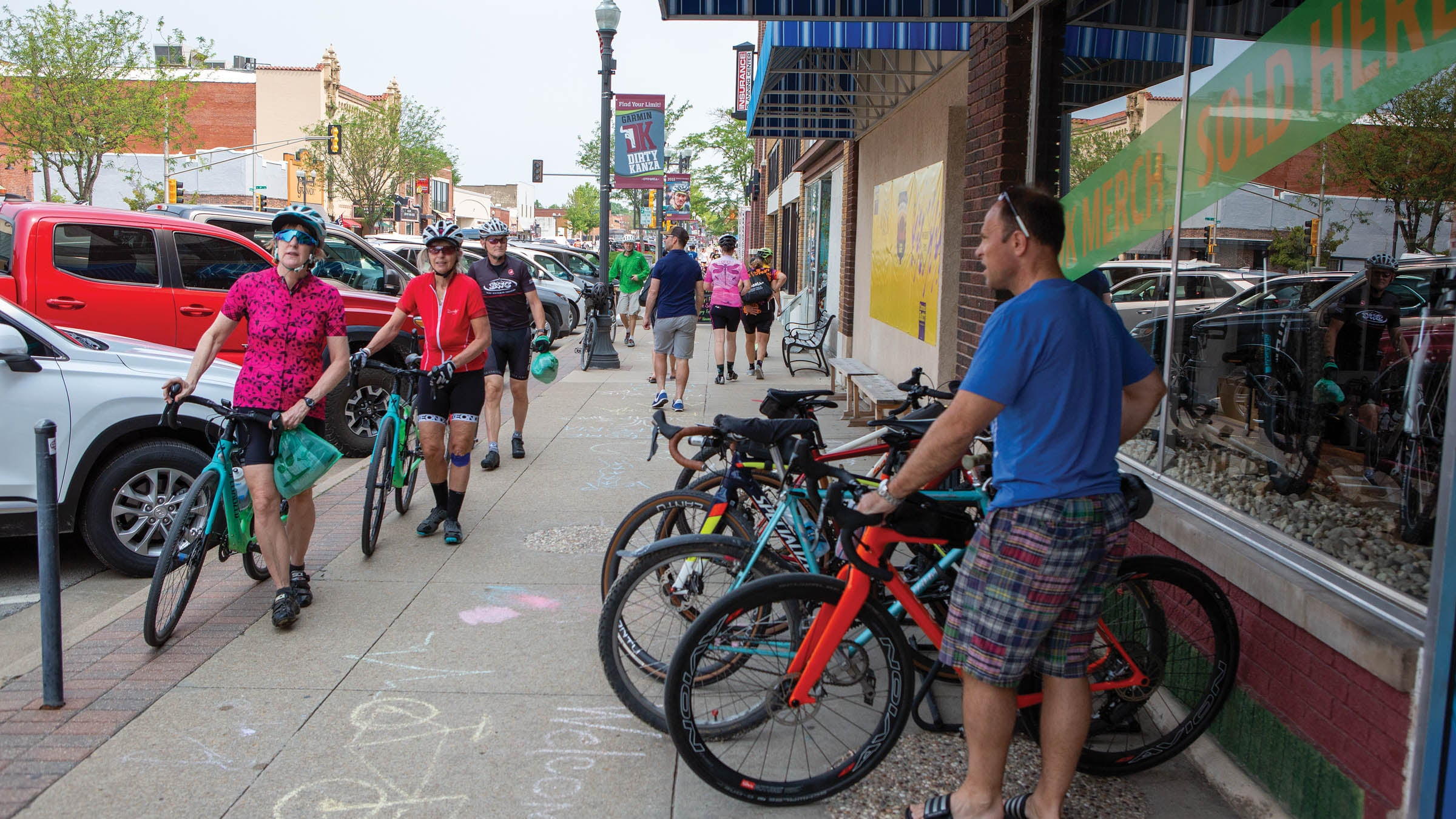 Cyclists line up their bikes outside a storefront in a small downtown area