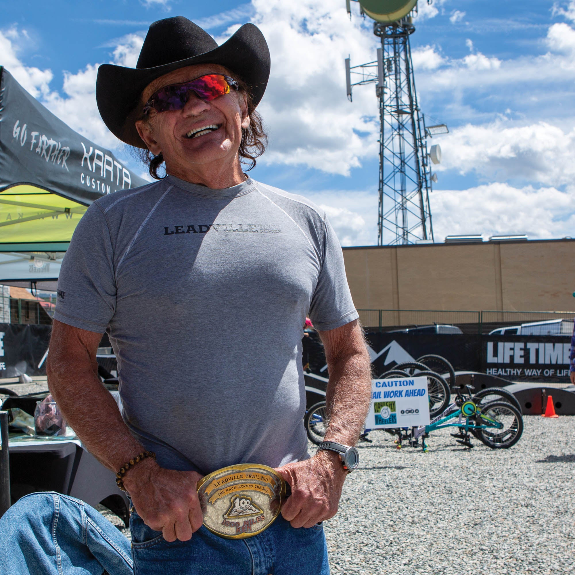 Chlouber smiling in a t-shirt, cowboy hat, and massive gold belt buckle