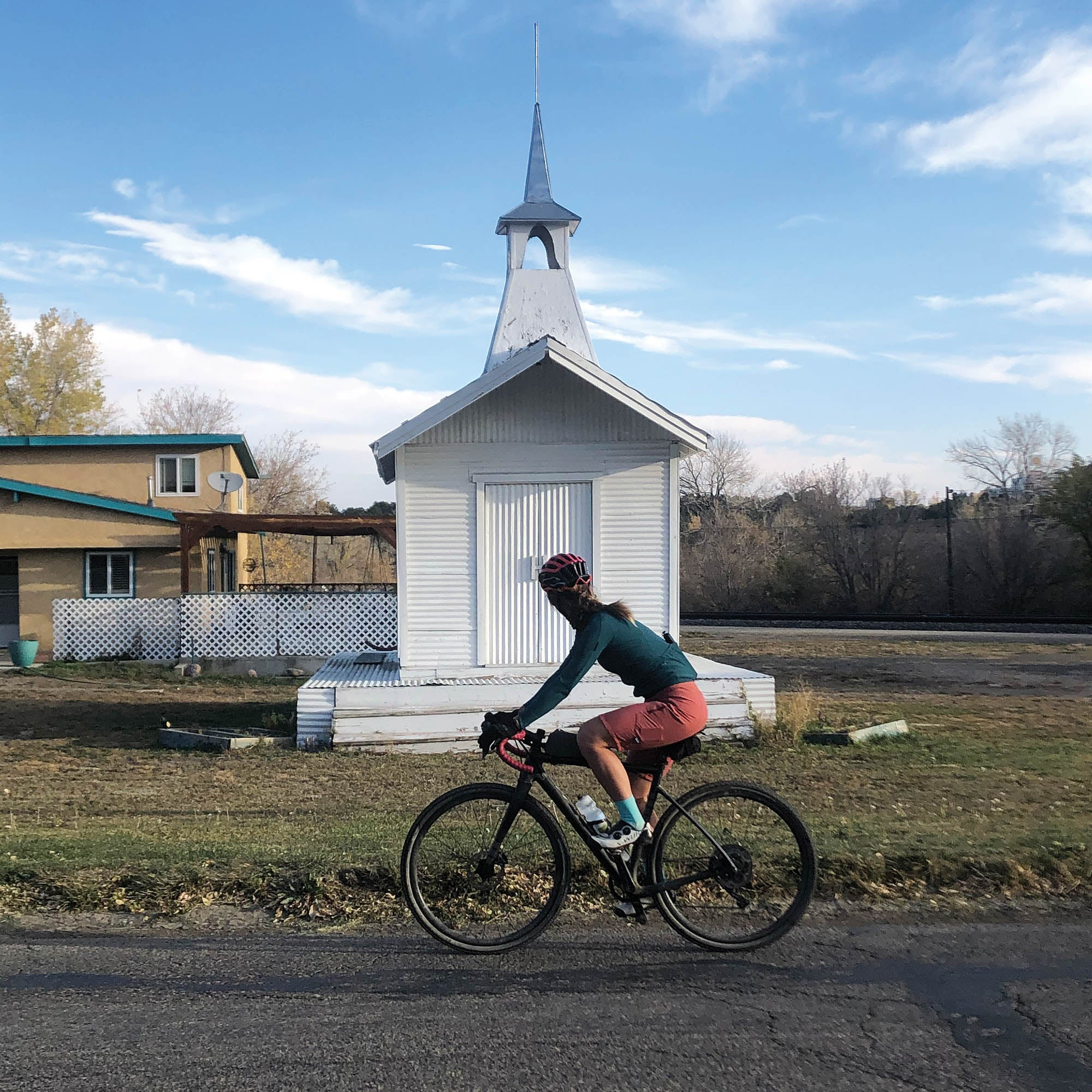 Woman on her bike, looking at a small white church